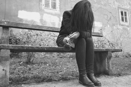 crying woman sitting along on a bench after a funeral